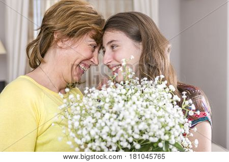 Woman And Her Daughter With A Bouquet Of Flowers In Their House. Mother's Day,