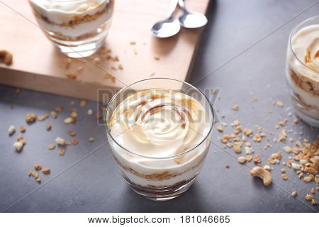 Glass with tasty yogurt dessert on table