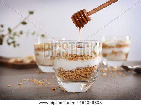 Pouring honey into glass with tasty yogurt dessert on table