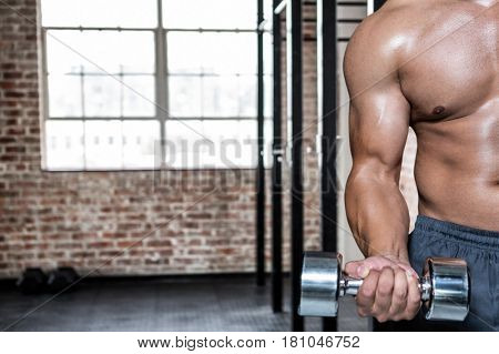 Digital composite of Midsection of man exercising with dumbbells at gym
