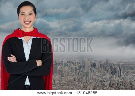 Digital composite of Portrait of smiling businesswoman wearing cape while standing against city