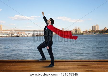 Digital composite of Side view of businessman wearing cape with arm raised standing by river against city