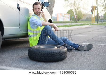 Man Calling Help Service For A Flat Tyre