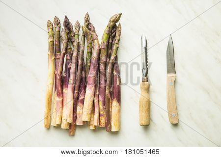 Fresh purple asparagus with knife and peeler.