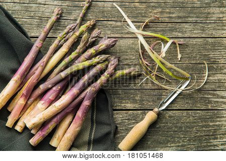 Fresh purple asparagus with peeler on old wooden table.