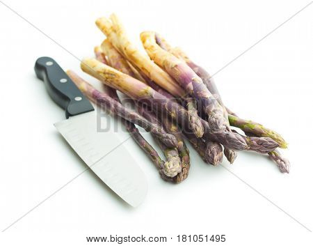 Fresh purple asparagus with knife isolated on white background.