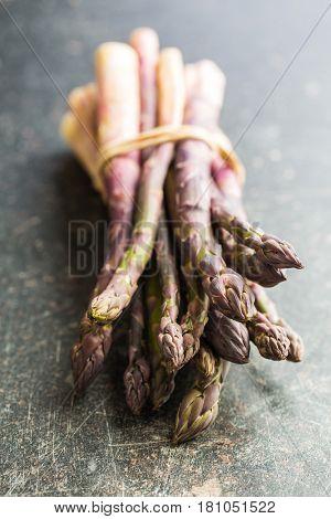Fresh purple asparagus on old kitchen table.