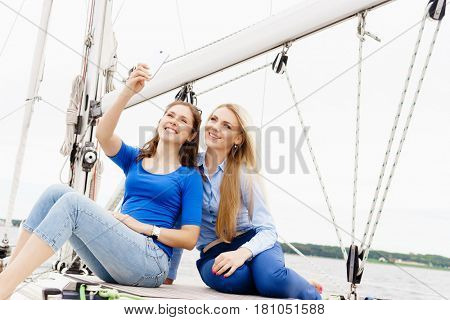 Two beautiful, attractive young girls taking selfie on a yacht. Traveling, vacation, tourism, concept.