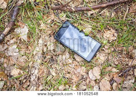 Close Up Picture Of A Broken Mobile Phone On A Ground In Park