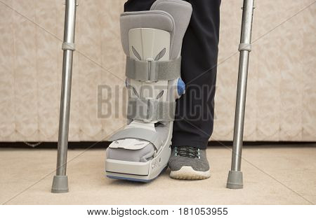 Unrecognisable woman wearing a medical orthopaedic boot with crutches