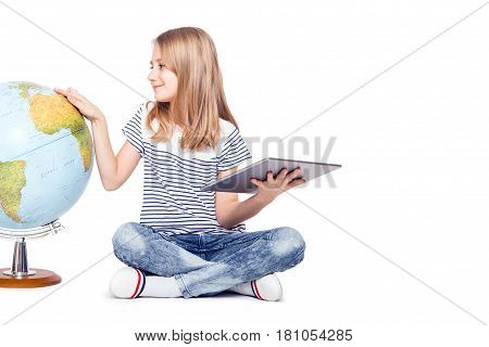 cute little young girl with tablet and globe. Schoolgirl using modern technology in teaching geography.