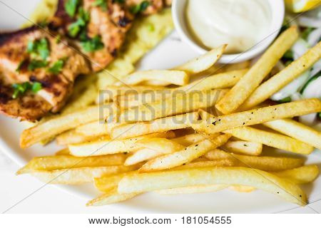 grilled meat with french fries close up.
