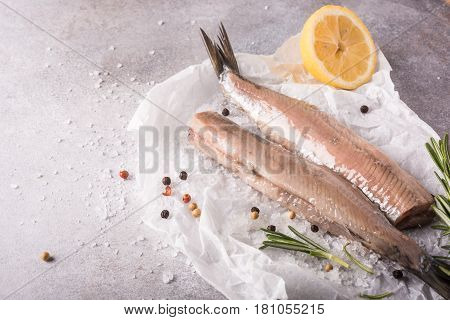 Freshly salted herring with salt, lemon ans rosemary on gray background with copy space. Traditional Dutch delicacy. Retro style toned.