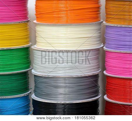 Reels of plastic for 3D printer close-up. Reels of filament wire for 3D printer different colors. Material produced from FDM printing technology. Many reels vertical view. Abstract modern background