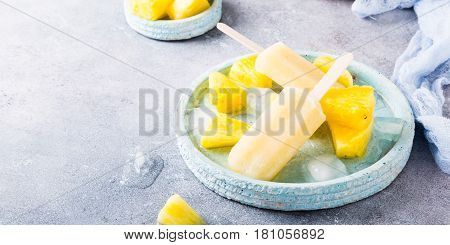 Delicious homemade pineapple popsicles on light blue plate on gray background. Summer food concept with copy space. High angle view.