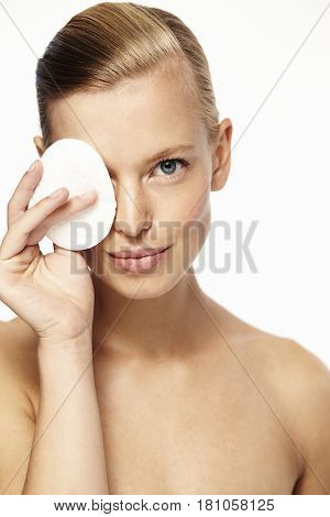 Beautiful  healthy young woman behind cotton pad portrait