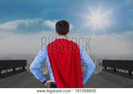 Digital composite of Rear view of businessman wearing cape while standing against sky