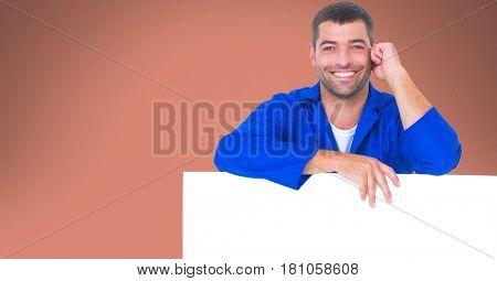 Digital composite of Portrait of worker leaning on blank bill board