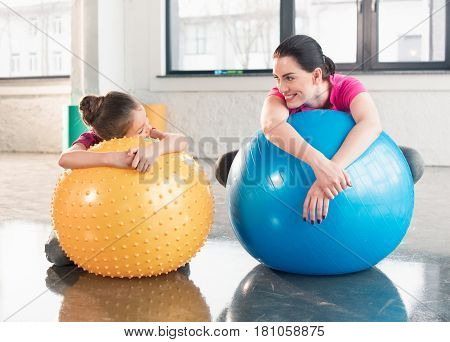 Happy Mother And Daughter Lying On Fitness Balls And Smiling Each Other