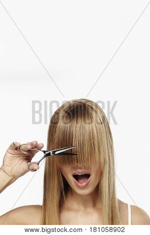 Blond girl with scissors about to cut fringe studio