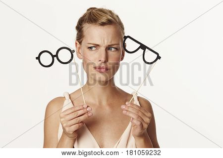 Stunning woman choosing pair of joke spectacles