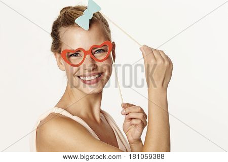 Beautiful woman holding bow tie and glasses disguise