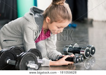 Cute Little Girl In Sportswear Sitting On Floor And Looking At Dumbbells In Gym