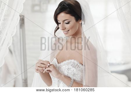 Happy bride looking at engagement ring in wedding-day.