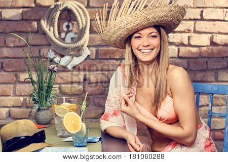 Happy young woman enjoying summer holiday in beach bar, smiling.