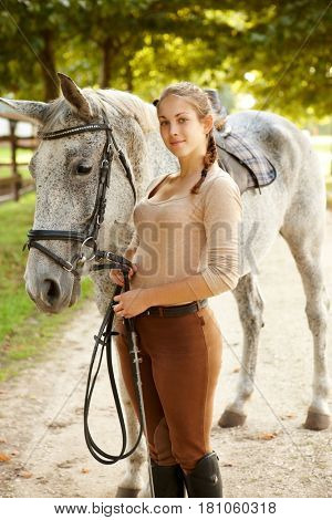Young woman standing by horse, holding leading-rein, looking at camera.