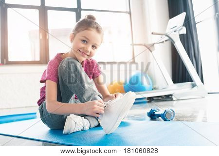 Adorable Girl In Pink Shirt Sitting On Yoga Mat And Tying Shoelaces In Gym