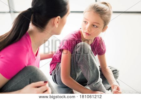 mother and daughter in pink shirts sitting on floor in gym