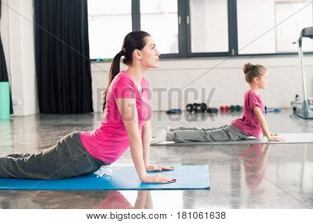 Mother And Daughter In Pink Shirts Practicing Yoga In Cobra Pose In Gym
