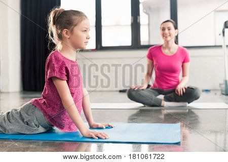 Mother In Lotos Pose And Daughter In Cobra Pose In Pink Shirts In Gym