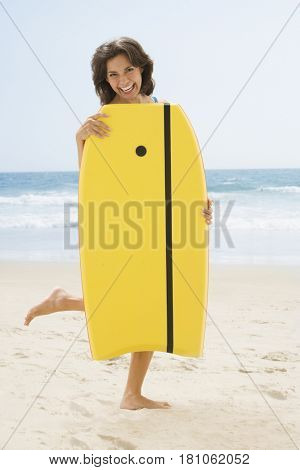Hispanic woman holding boogie board