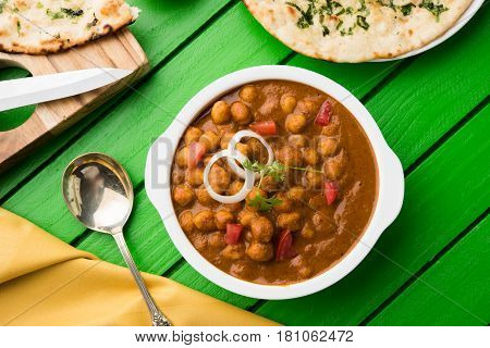 spicy chick peas curry or Chola Masala or Chana Masala or chole bhature or choley garnished with sliced onion and green coriander leaf, selective focus