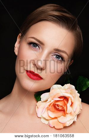 Portrait of young beautiful glamorous woman with red lipstick and flower