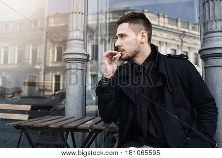 Man took sit to have cigarete, looking away thoughtfully. Magnificent city view on background.