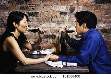 Asian couple drinking wine