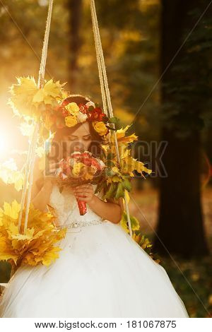 Bride Holds A Red Wedding Bouqet In Her Arms Sitting On The Swing Illuminated With Autumn Sun