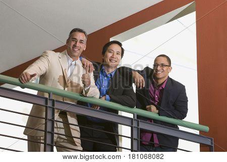 Multi-ethnic businessmen leaning on railing