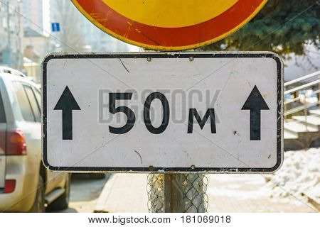 Closeup image of plate saying 50 meters under road sign