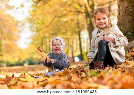 Beautiful sisters in the warm autumn light with golden leaves on trees