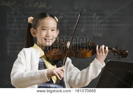Asian girl playing violin in front of blackboard