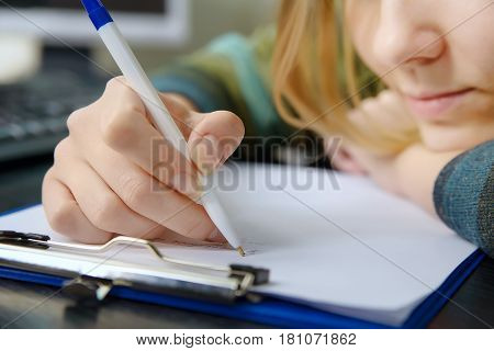 Young woman writing something with white pen on paper sheet with computer in background