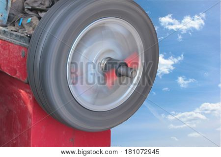 The wheel rotates on the balancing machine on the background of sky with clouds