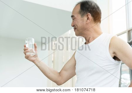 Asian senior man holding glass of water at a gym. Tired thirstily. freshness.