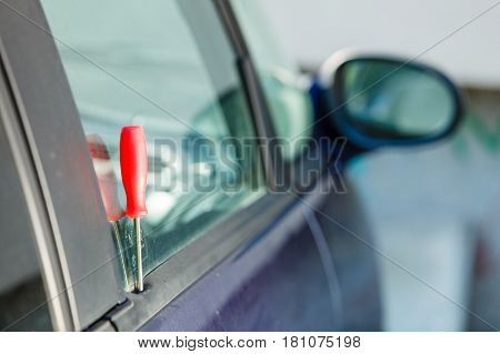 Anti theft system problem concept. Red screwdriver in car door after burglary