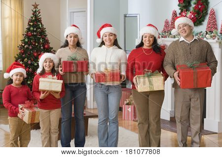 Hispanic family wearing Santa Claus hats and holding gifts