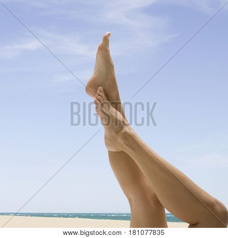 Asian woman's bare legs at beach
